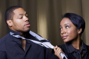 An attractive african american woman is suggestively pulling her lover's tie.