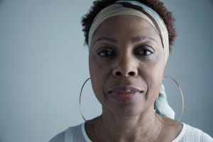 Close up portrait serious African American mature woman wearing headscarf and large hoop earrings