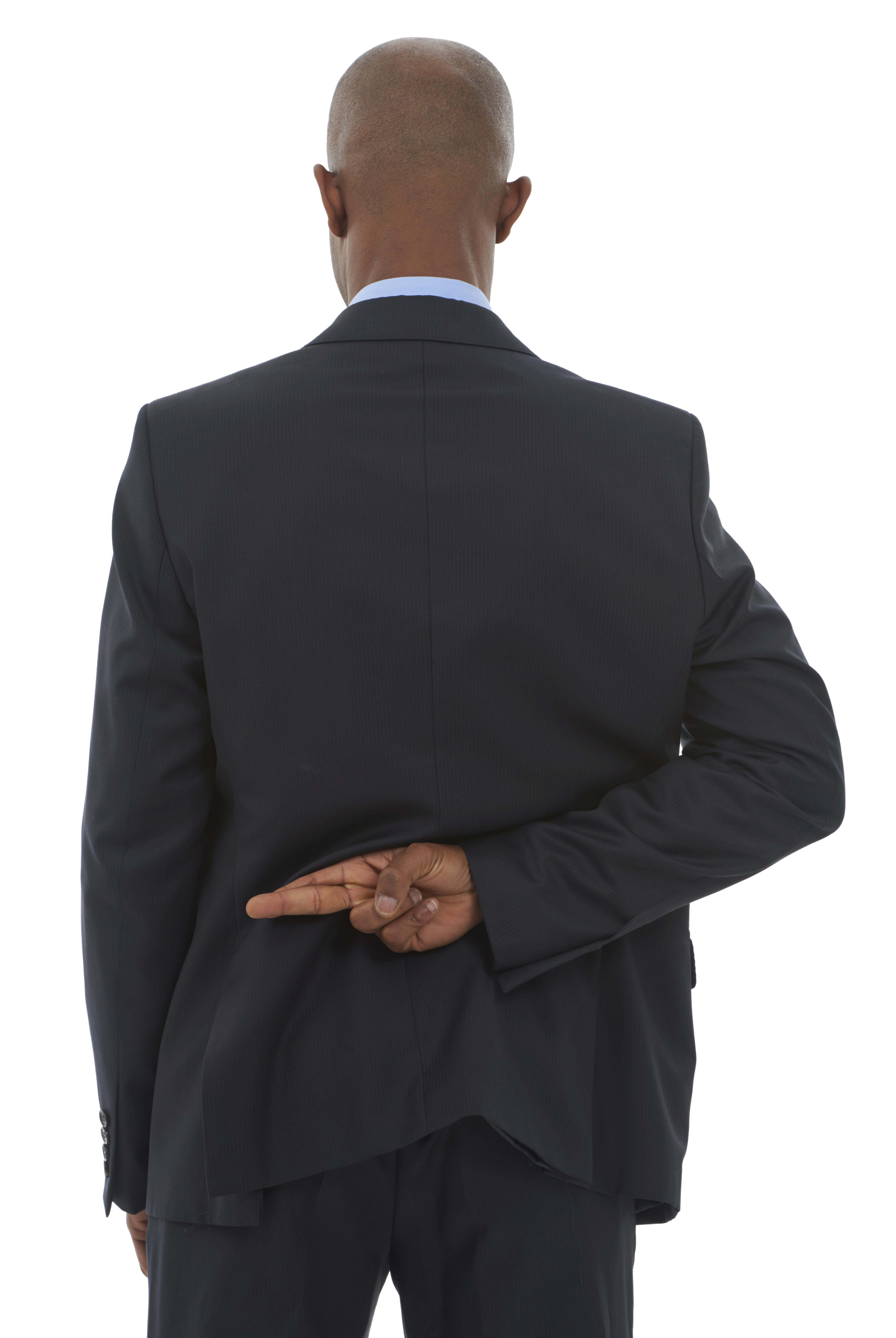 An African-American businessman with his fingers crossed behind his back
