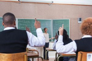 Medium POV of the back of students with their hands raised in classroom, Cape Town, South Africa