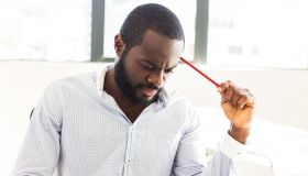 African businessman thinking hard.