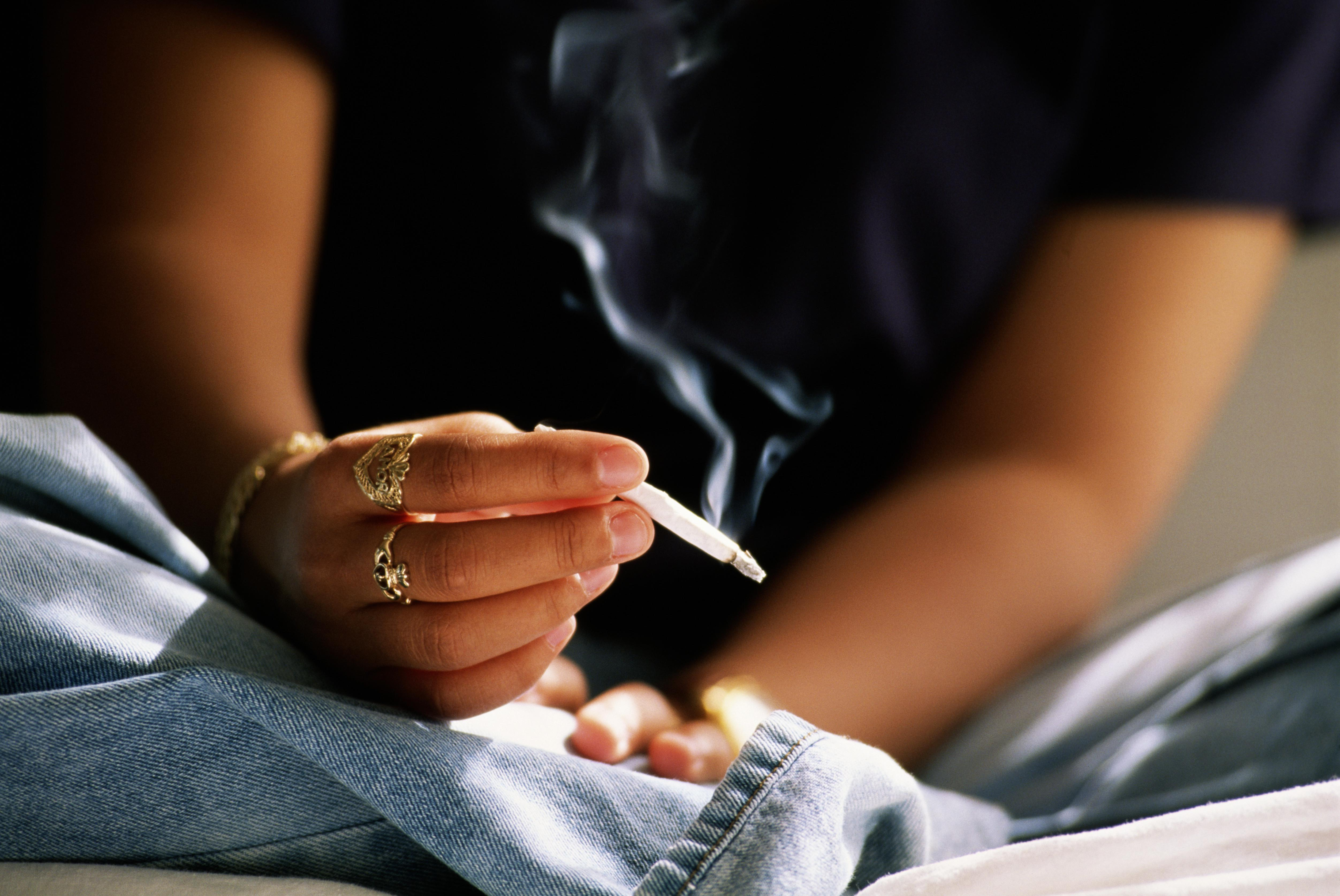 Teenager (16-18) smoking hand rolled cigarette