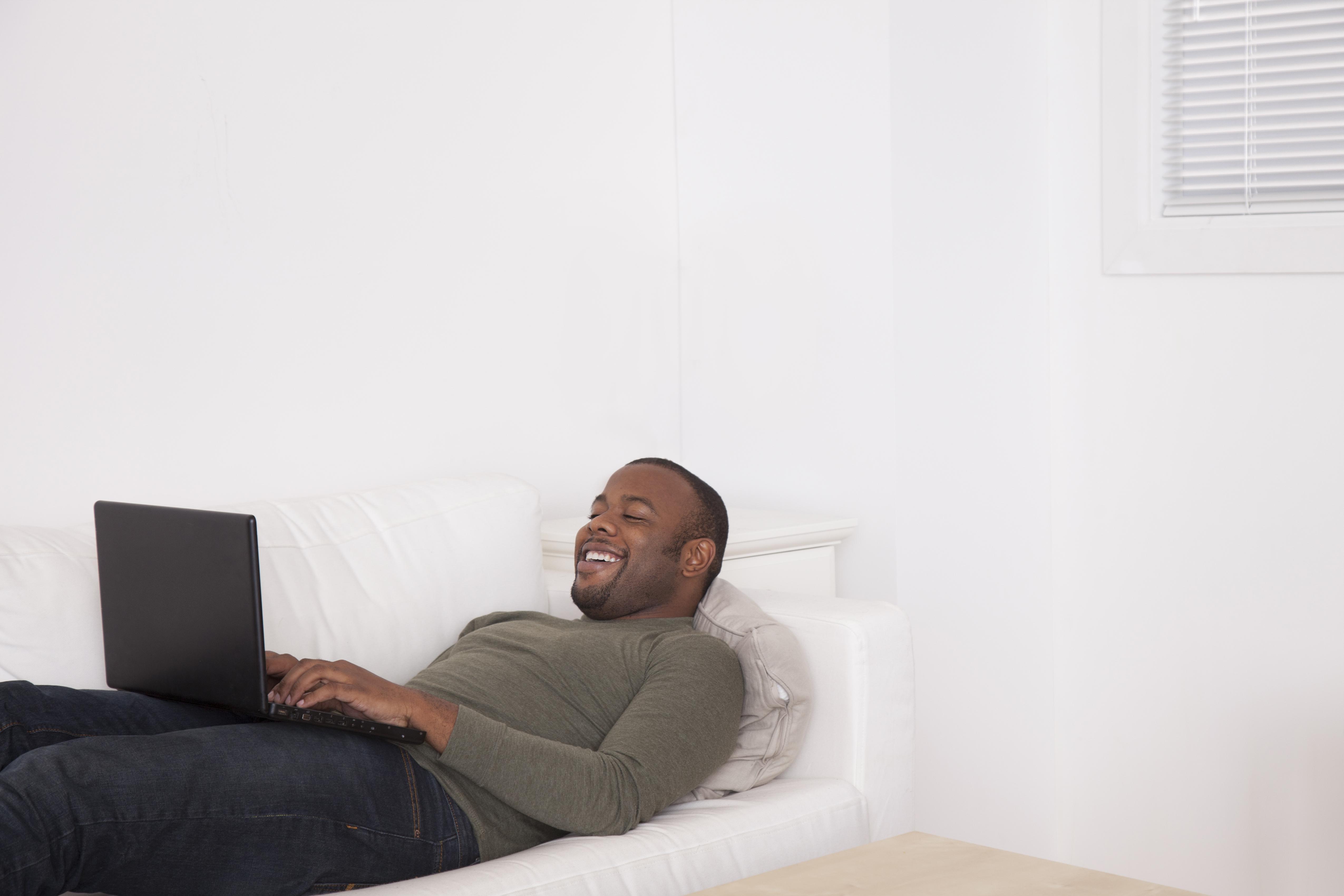Black man laying on sofa using digital tablet