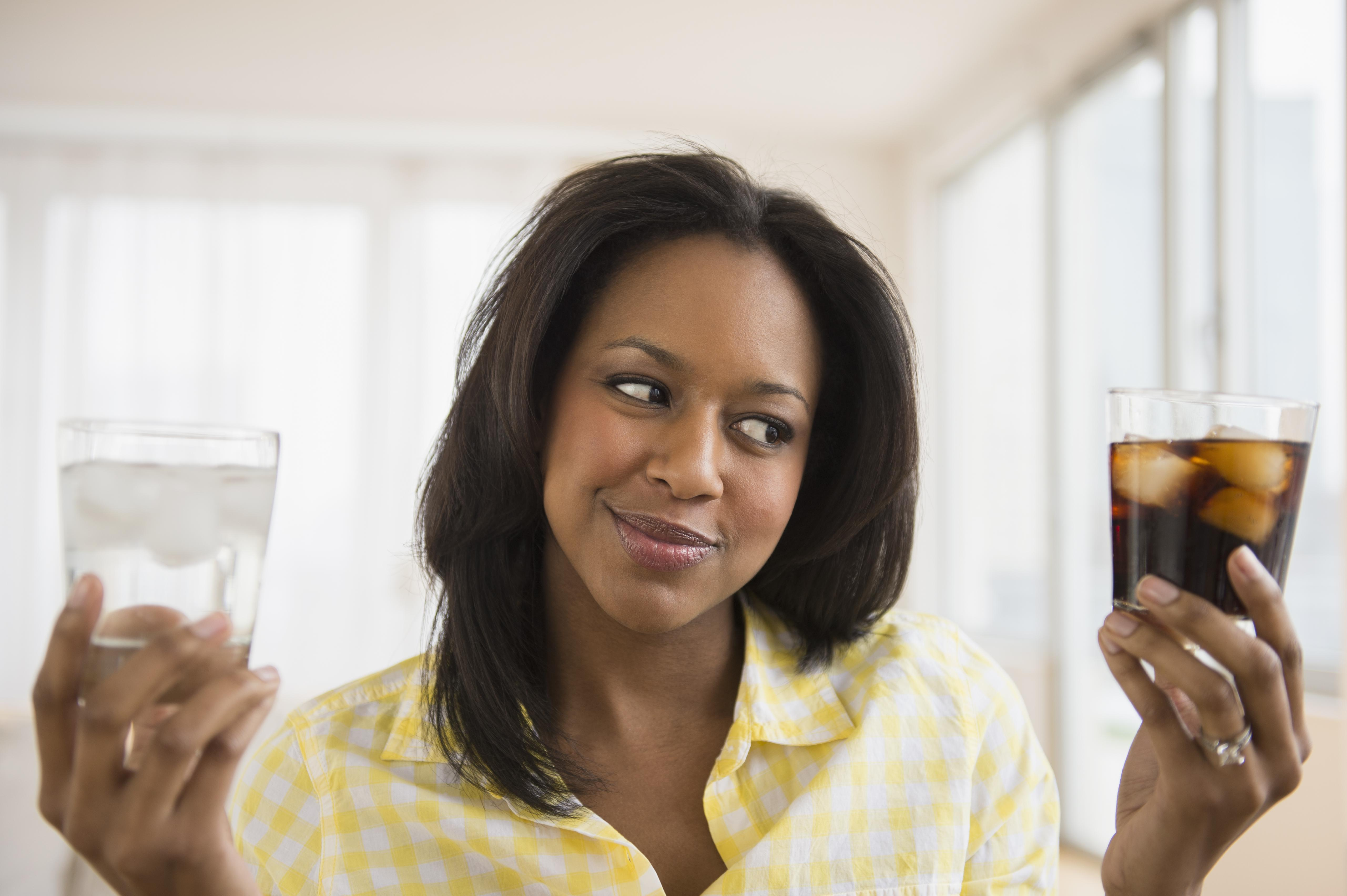 African American woman choosing water or soda