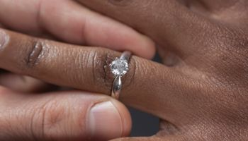 Close up of man putting engagement ring on girlfriend