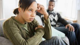 Boyfriend watching frustrated girlfriend on sofa