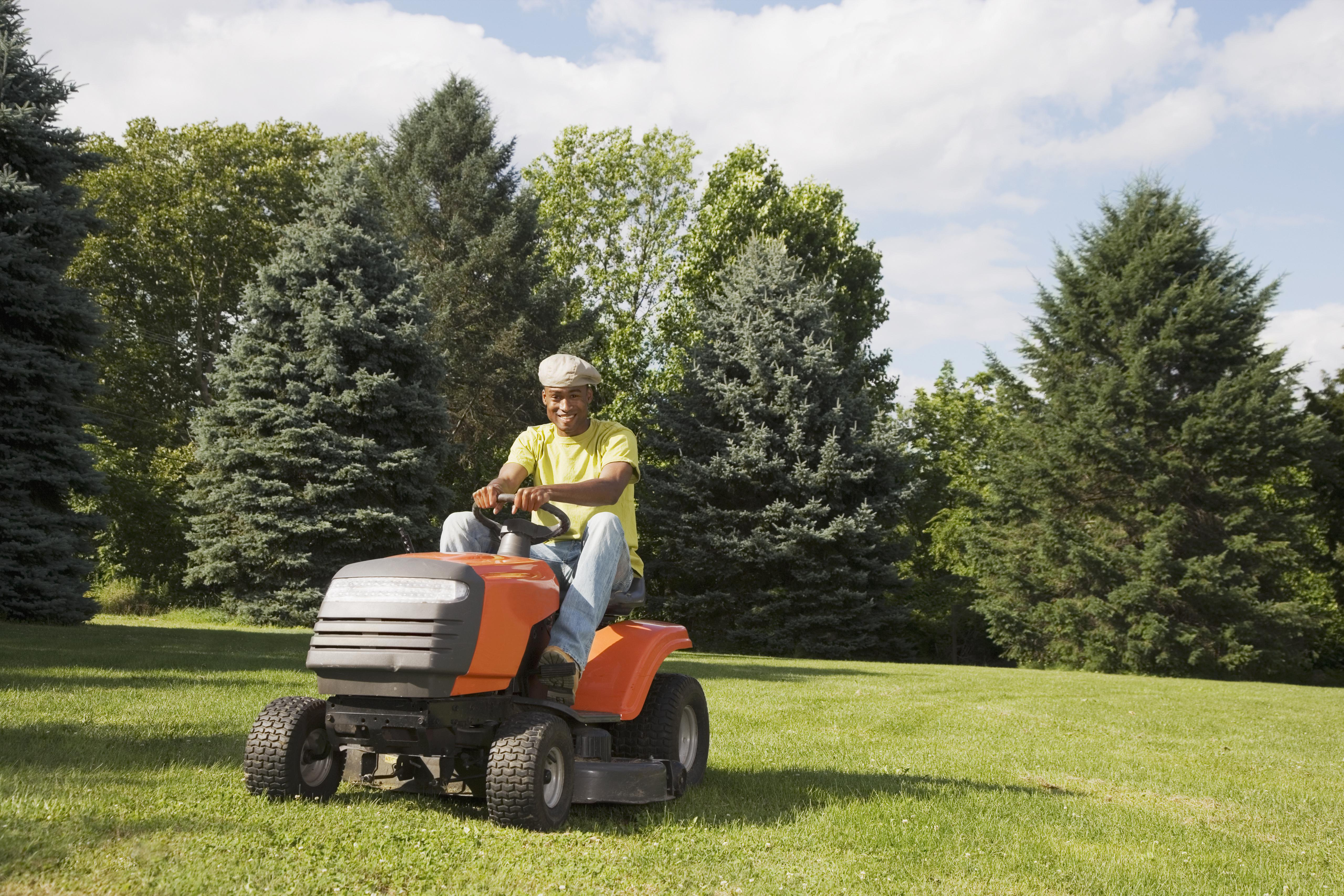 African American man mowing lawn