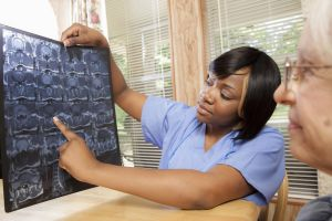 Medical: Home healthcare nurse reviews x-ray with senior woman.