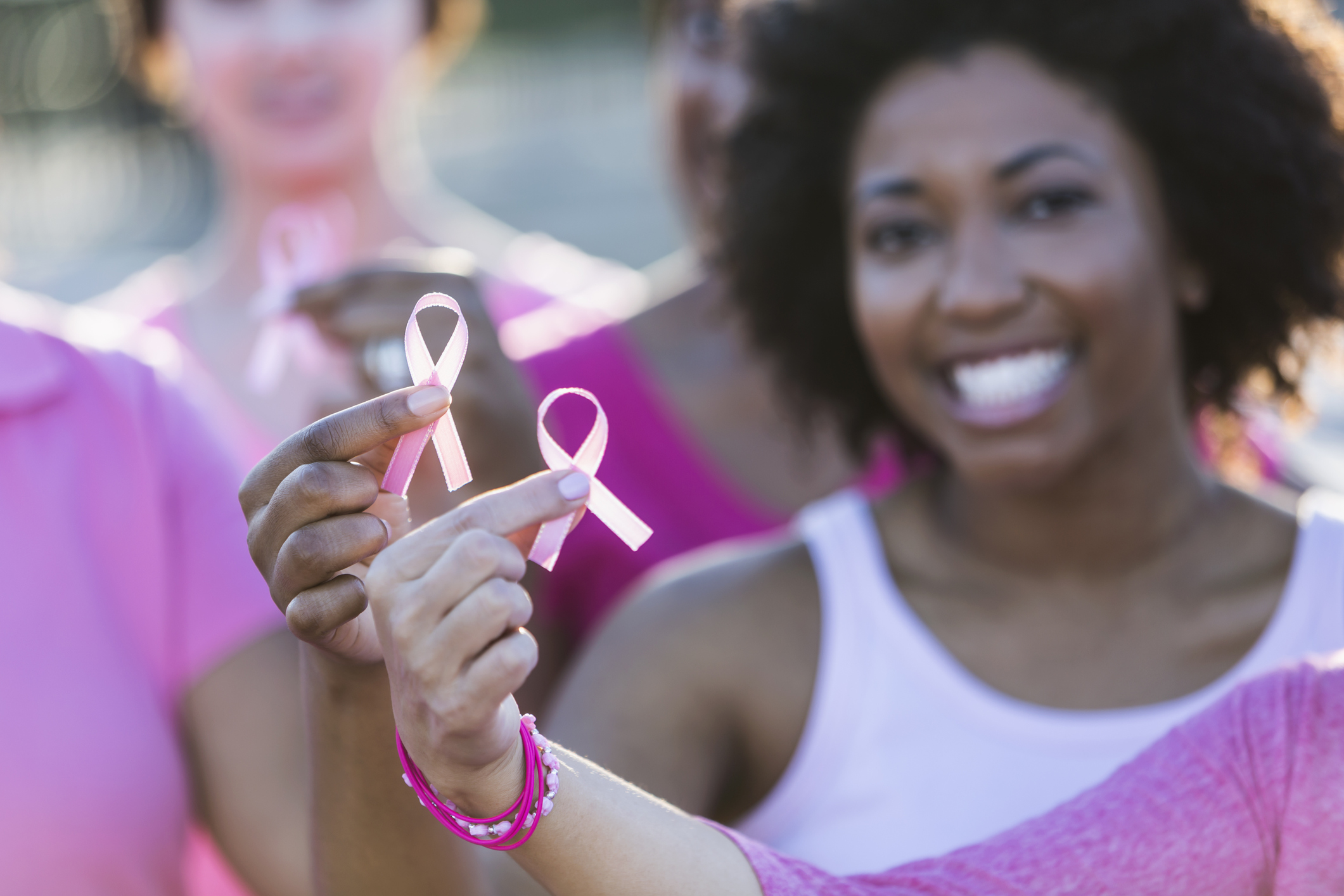 Multiracial women holding breast cancer awareness ribbon