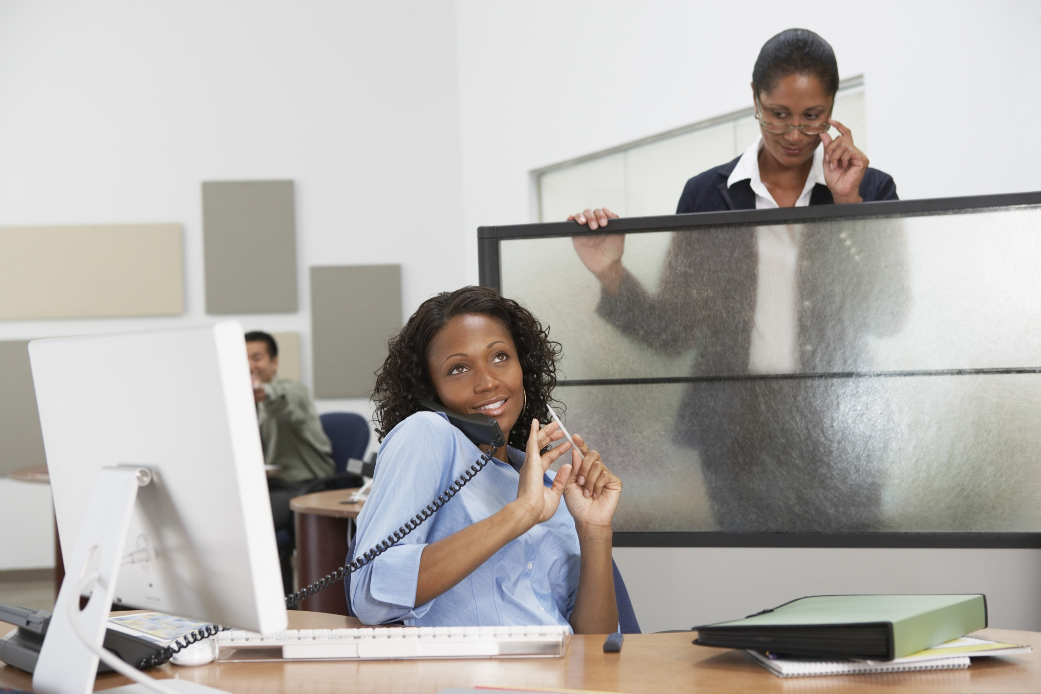 African businesswoman filing fingernails at desk with boss looking over cubicle wall