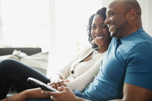 Happy couple sitting with remote control at home