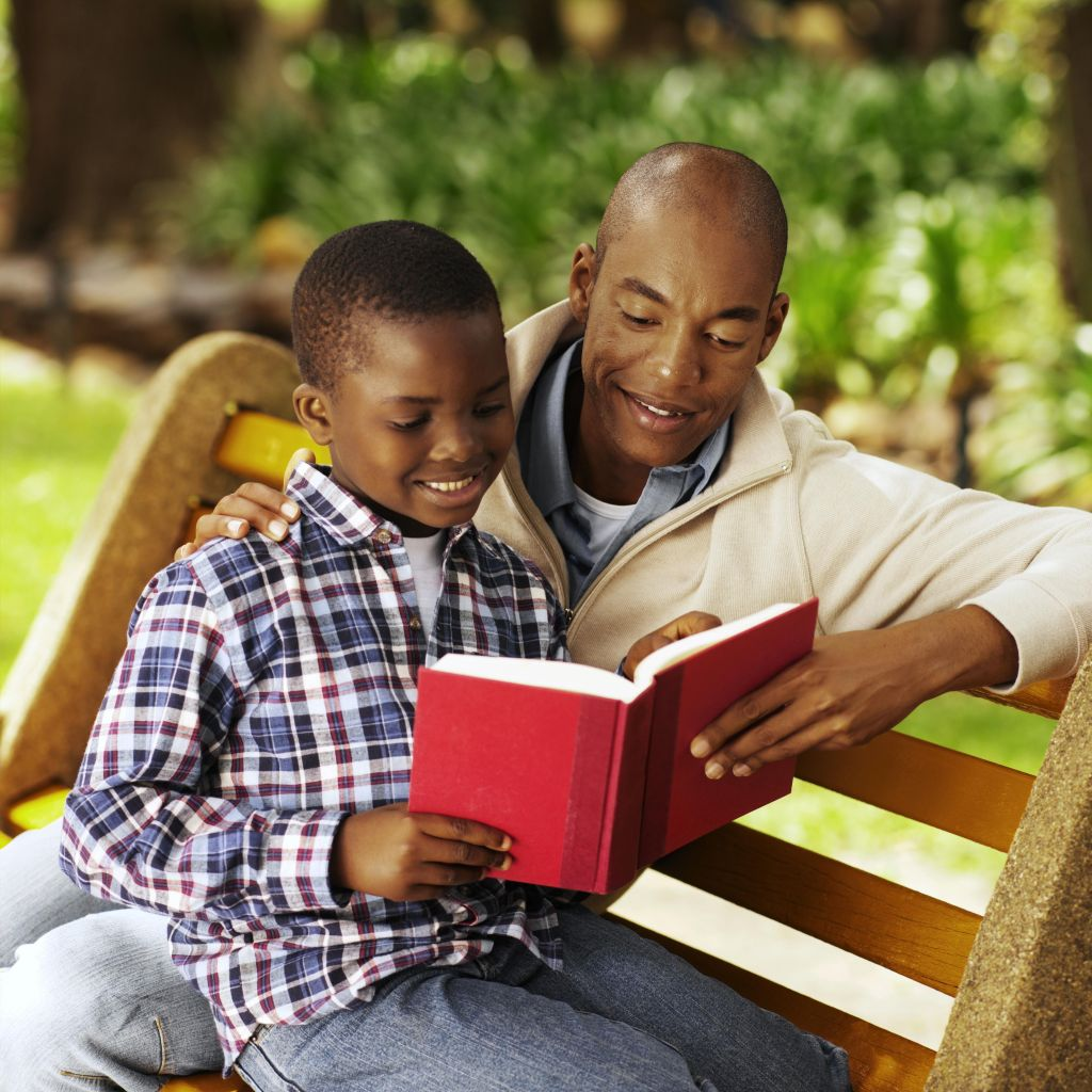 Close-up of father and son sitting on bench reading book (10-11)