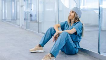 Tired Female Medical Professional Taking Break in Hospital Corridor